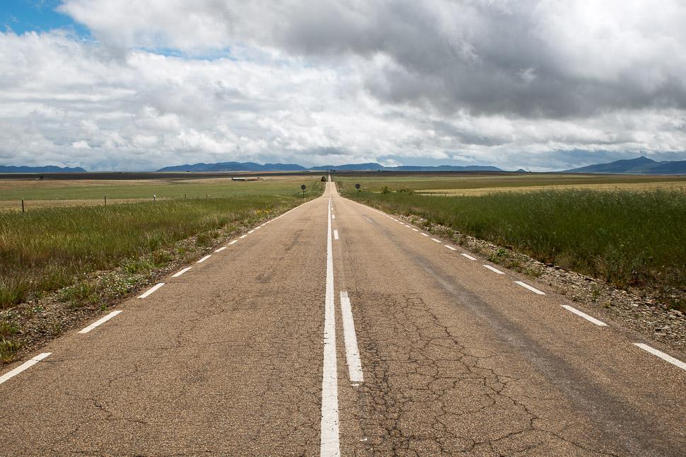 schnurgerade Straße in spanischer Steppenlandschaft
